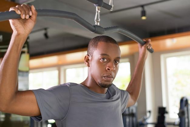Der ernste schwarze mann, der auf lat trainiert, ziehen maschine herunter Kostenlose Fotos