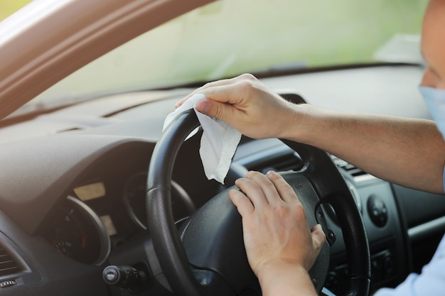 Der fahrer reinigt das lenkrad seines autos mit einem antibakteriellen tuch. antiseptisches, hygiene- und gesundheitskonzept. selektiver fokus Premium Fotos