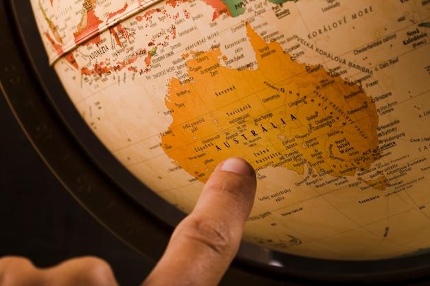Der finger einer person, der auf australien-land auf kugel zeigt Kostenlose Fotos