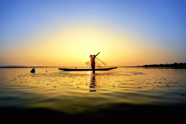 Der fischer warf ein boot auf sein boot. Premium Fotos