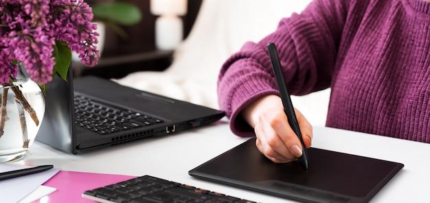 Der freiberufliche grafiker arbeitet von zu hause aus. frau zeichnet auf grafiktablett im heimbüro unter verwendung des laptops und des computers. fernarbeit im gemütlichen heimbüro mit blumen. Premium Fotos