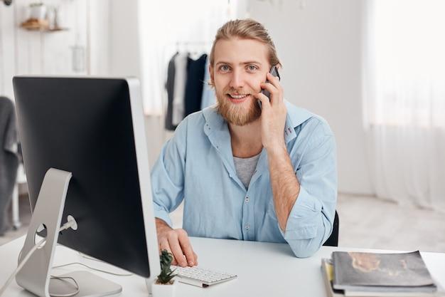 Der fröhlich lächelnde bärtige männliche student erhält einen anruf von einem freund, sitzt im hellen büro, trägt ein blaues hemd und beendet bald die arbeit. hübscher männlicher freiberufler hat telefongespräch, diskutiert ideen. Kostenlose Fotos