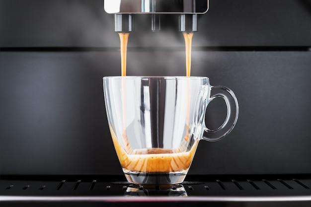 Der gebrühte kaffee wird aus der kaffeemaschine in eine glastasse gegossen Premium Fotos