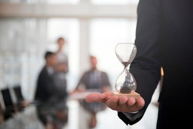 Der geschäftsmann, der ein stundenglas hält, bedeutet die wichtigkeit, rechtzeitig zu sein Kostenlose Fotos