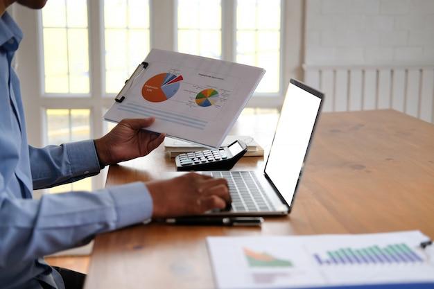 Der geschäftsmann, der mit dokument arbeitet, startmann analysieren finanzdaten am arbeitsplatz, Premium Fotos