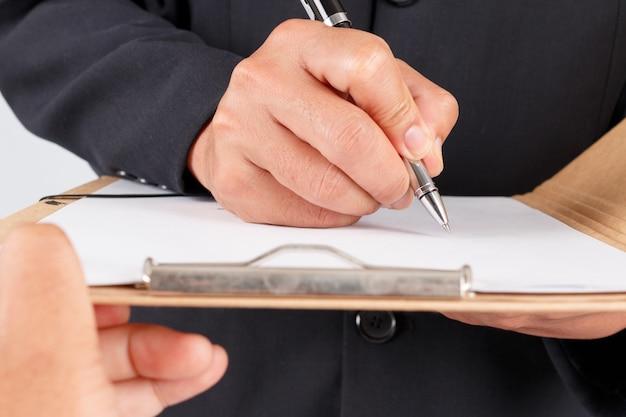 Der geschäftsmann, der mit dokumenten arbeitet, unterzeichnen vertrag Premium Fotos