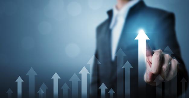 Der geschäftsmann, der zukünftiges unternehmenswachstum des pfeildiagramms zeigt, planen und erhöhen prozentsatz Premium Fotos