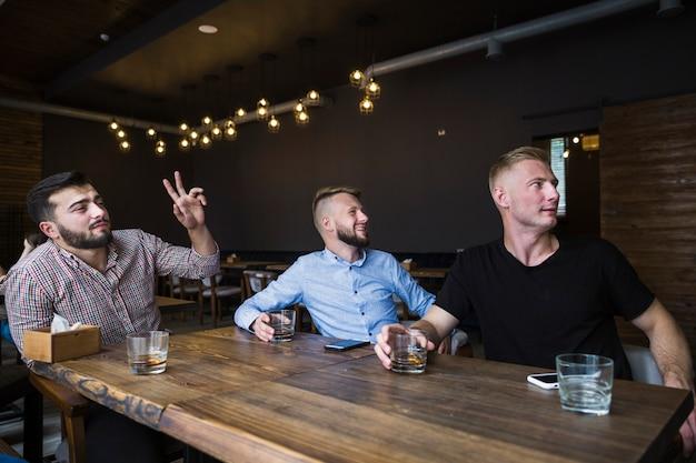 Der gestikulierende mann beim trinken dinks mit seinen freunden in der bar Kostenlose Fotos