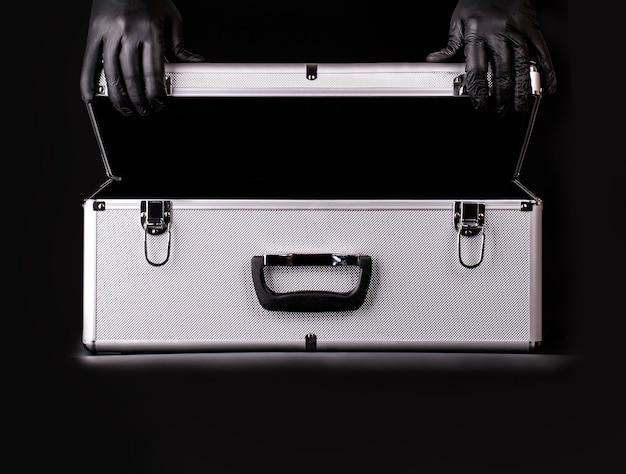 Der große aluminiumkoffer und die hände schwarzer sicherheitshandschuhe Premium Fotos