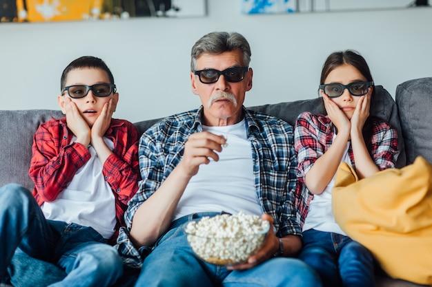 Der großvater von eldery, der mit seinen enkeln auf dem sofa im wohnzimmer sitzt und sich einen horrorfilm ansieht, isst popcorn. Premium Fotos