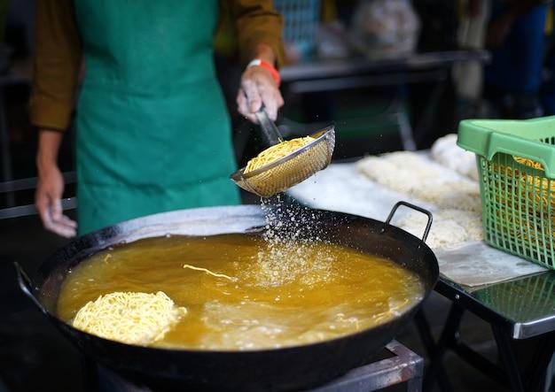 Der händler brät knusprige gelbe nudeln auf dem bratrost in einer großen pfanne mit heißem öl. knusprige eiernudeln für nudeln in dick-chinesisch-thailändischer soße. Premium Fotos