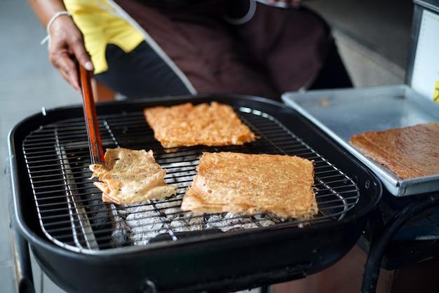Der händler hat in scheiben geschnittene blätter aus getrocknetem und gewürztem knusprigem schweinefleisch gegrillt, um sie auf dem holzkohleofengrill zu erhitzen. Premium Fotos
