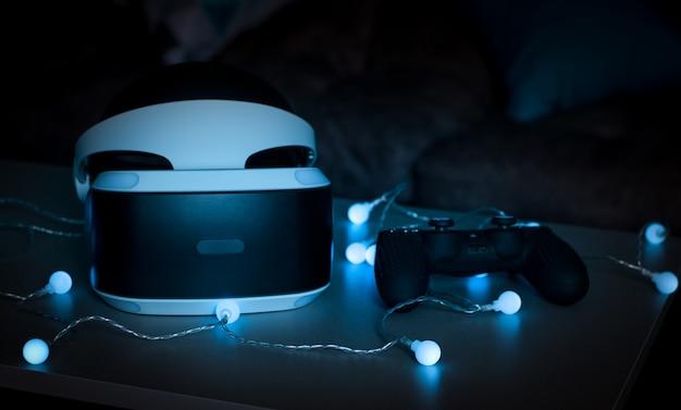 Der helm der virtuellen realität. neue erfahrung im spiel. erstaunliche emotionen, kühle ruhe. virtual-reality-brillen liegen in neonlichtern. Premium Fotos