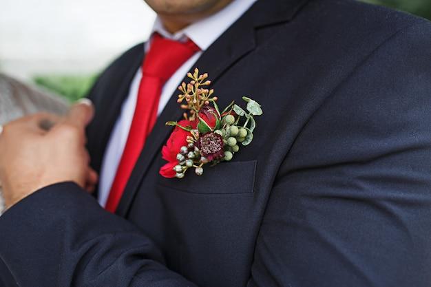Der hochzeitsboutonniere des bräutigams aus sukkulenten und roten blumen in einer schwarzen jacke mit roter krawatte Premium Fotos