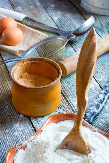 Der holzlöffel klebte mit dem mehl, einem glas mit salz, eiern und nudelholz an der keramikschale Premium Fotos