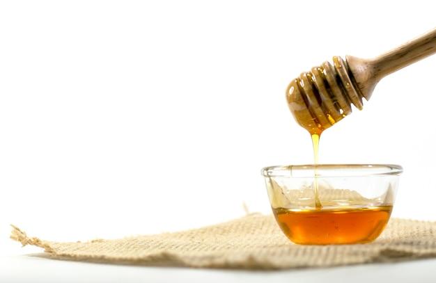 Der honiglöffel und duftender honig in eine transparente schüssel Premium Fotos