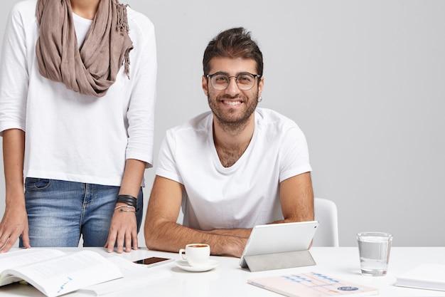Der hübsche bärtige unternehmer und seine nicht wiedererkennbare sekretärin arbeiten beim projekt zusammen Kostenlose Fotos
