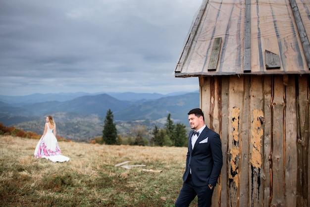 Der hübsche bräutigam steht in der nähe des hauses Premium Fotos