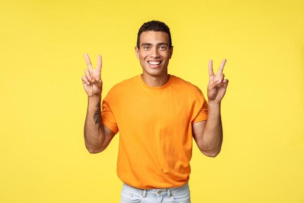 Der hübsche frohe junge mann im orange t-shirt, lächelnd optimistisch, lassen friedensgeste oder -zitate unterzeichnen und stehen gelben hintergrund, drücken bestimmtheit und optimismus aus und stehen gelben hintergrund Premium Fotos