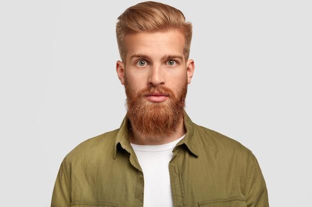 Der hübsche hipster hat einen ingwerbart, eine trendige frisur, schaut ernsthaft direkt in die kamera und denkt über zukünftige jobs nach Kostenlose Fotos