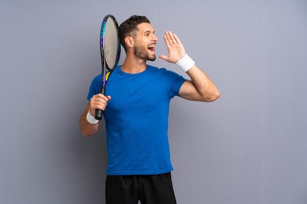Der hübsche junge tennisspielermann, der mit dem breiten mund schreit, öffnen sich Premium Fotos
