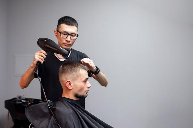 Der hübsche kerl hat einen haarschnitt in einem friseurladen Premium Fotos