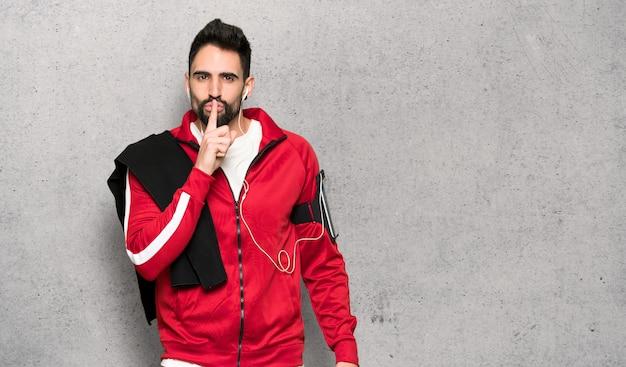 Der hübsche sportler, der ein zeichen der ruhe zeigt, gestikulieren finger in mund über strukturierter wand Premium Fotos