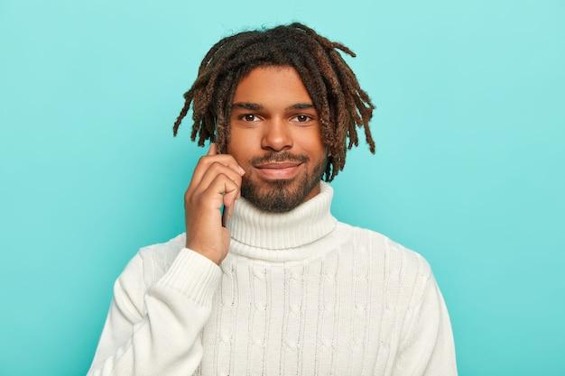 Der hübsche unrasierte mann hält ein modernes mobiltelefon in der nähe des ohrs, führt telefongespräche, trägt einen warmweißen pullover, hat einen bart und dreadlocks Kostenlose Fotos