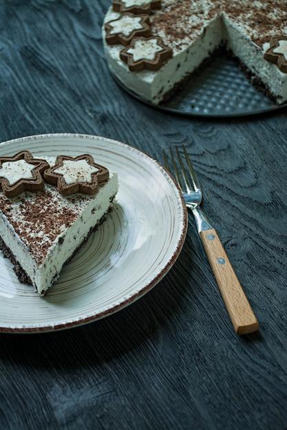 Der hüttenkäsekuchen ist mit keksen und geriebener schwarzer schokolade auf dunklem holz dekoriert Premium Fotos