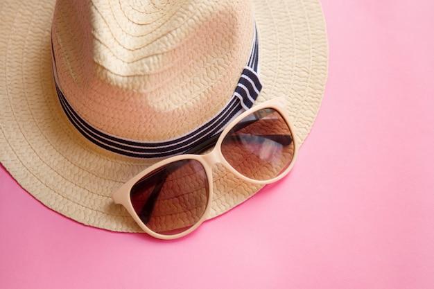 Der hut der strohstrandfrau mit sonnenbrillen auf rosa ebenenlage. ansicht von oben. sommerausflug. Premium Fotos