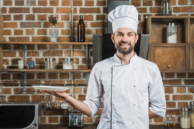 Der hut des glücklichen kochs tragender chef, der in der hand eine leere platte hält Kostenlose Fotos
