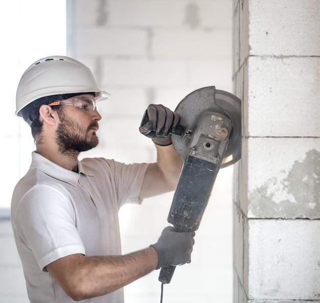 Der industriebauer arbeitet mit einem professionellen winkelschleifer, um ziegel zu schneiden und innenwände zu bauen Kostenlose Fotos