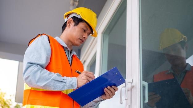 Der inspektor oder ingenieur überprüft die gebäudestruktur und die türspezifikationen. nach der renovierung ist abgeschlossen Premium Fotos