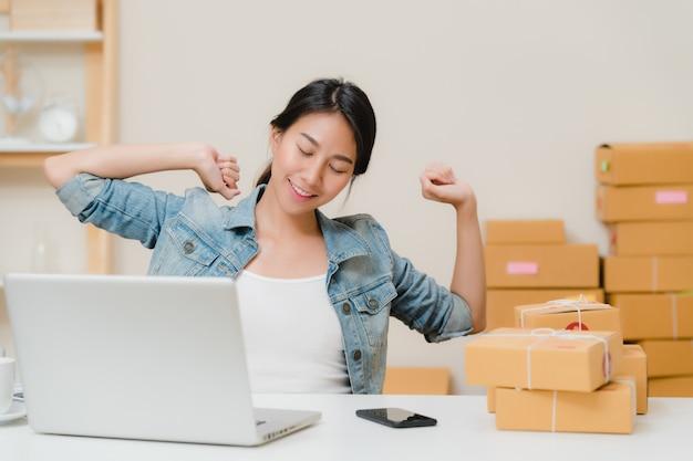 Der intelligente asiatische jungunternehmergeschäftsfrauinhaber von kmu, der arbeitet und sich entspannen, heben hoch und nahes auge vor laptop-computer auf schreibtisch zu hause an. Kostenlose Fotos