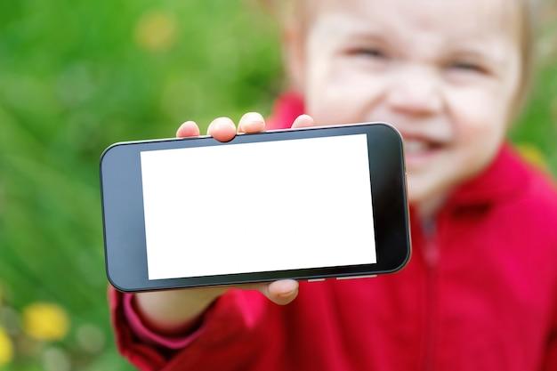 Der intelligente telefonschirm der show des kleinen mädchens mit leerem weißem kopienraum. Premium Fotos