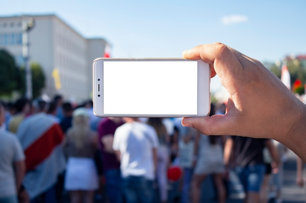 Der journalist hält ein smartphone in der hand und fotografiert protestierende aktivisten in belarus. Premium Fotos
