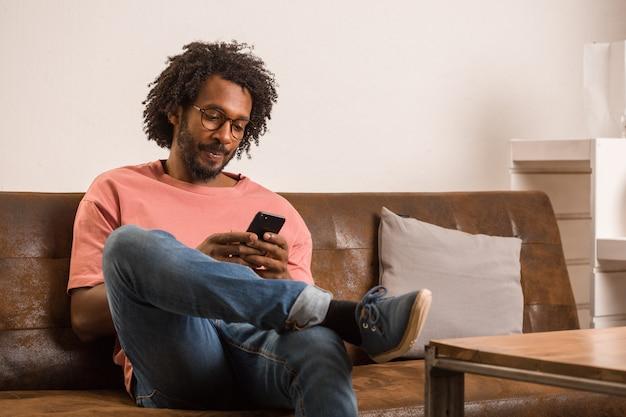 Der junge afrikanische mann, der auf mobile spricht und auf einem sofa sitzt, lächelt und positiv. Premium Fotos