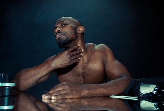 Der junge afrikanische mann im schlafzimmer sitzt vor dem spiegel, nachdem er sich zu hause den bart gekratzt hat. konzept der menschlichen emotionen Kostenlose Fotos