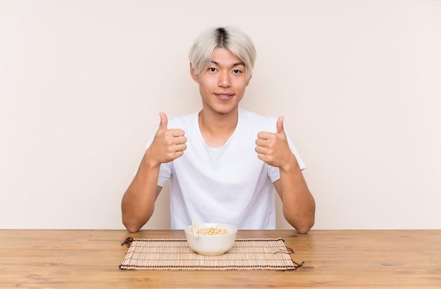 Der junge asiatische mann mit dem ramen in einer tabelle gebend daumen up geste Premium Fotos