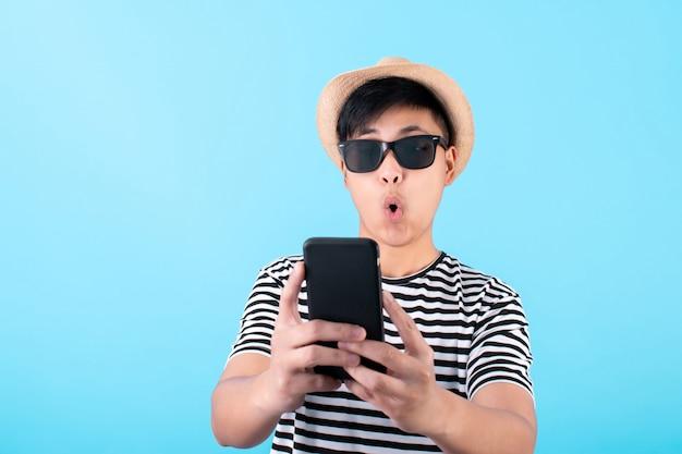 Der junge asiatische reisende ist schockiert über ein smartphone auf blau Premium Fotos