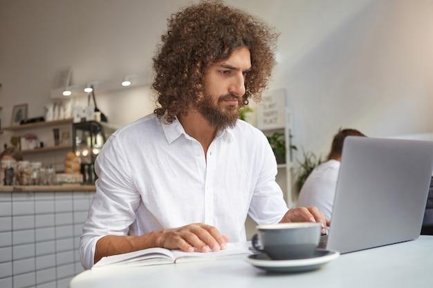 Der junge attraktive bärtige geschäftsmann, der mit seinen arbeitsnotizen und seinem modernen laptop außerhalb des büros arbeitete und öffentliches wlan im café nutzte, konzentrierte sich auf seinen job Kostenlose Fotos