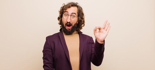 Der junge bärtige verrückte mann, der erfolgreich und zufrieden ist und mit dem breiten mund lächelt, öffnen sich und machen okayzeichen mit der hand gegen flache farbwand Premium Fotos