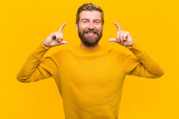 Der junge blonde mann, der eigenes lächeln mit beiden händen gestaltet oder umreißt, schaut positiv und glücklich, wellnessorangenwand Premium Fotos