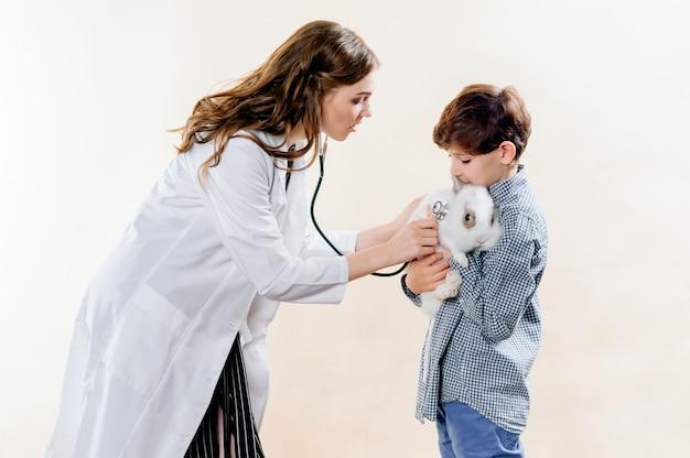 Der junge brachte sein kaninchen zur untersuchung zum tierarzt, der tierarzt macht eine untersuchung Premium Fotos
