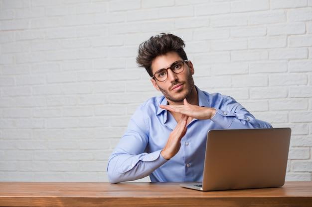 Der junge geschäftsmann, der an einem laptop sitzt und arbeitet, ermüdet und gelangweilt Premium Fotos