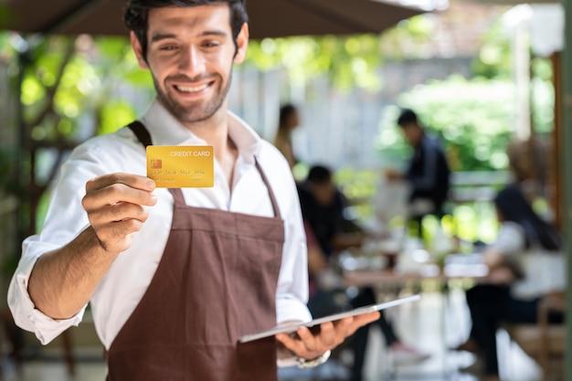 Der junge, gutaussehende geschäftsmann besitzt ein café mit einem tablet und einer kreditkarte, um den kunden zu sagen, dass sie für den gesamten service bar bezahlen sollen Premium Fotos