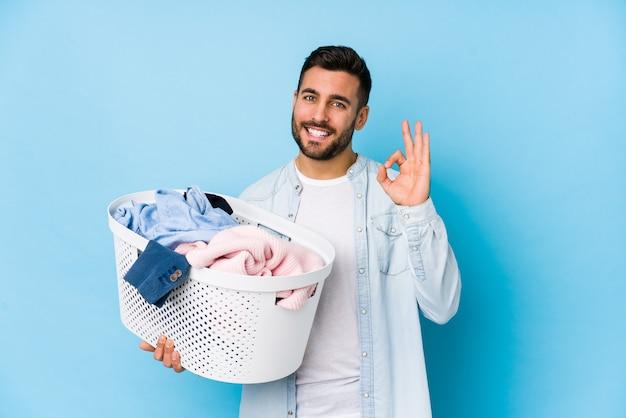 Der junge gutaussehende mann, der wäscherei tut, lokalisierte die nette und überzeugte vertretung der okaygeste. Premium Fotos