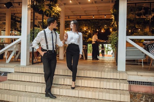 Der junge, gutaussehende mann hilft der frau, die treppe des sommerterrassencafés hinunterzugehen Premium Fotos