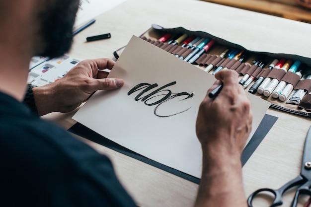 Der junge hipster-illustrator-künstler im schwarzen einfachen t-shirt schafft authentische und einzigartige handbeschriftungszeichnung in seinem hellen industriestudio Kostenlose Fotos