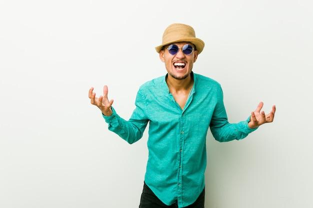 Der junge hispanische mann, der einen sommer trägt, kleidet das schreien mit raserei. Premium Fotos